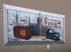 The Crosley radio ad depicts one of the company's famous radios and a Crosley car in front of the Crosley Empire's huge factory and radio tower.