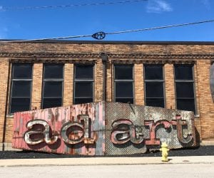 """A giant metal installation in front of the vacant old Crosley Building building and features the words """"ad art."""""""