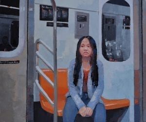 A young woman sits along on a New York subway. car