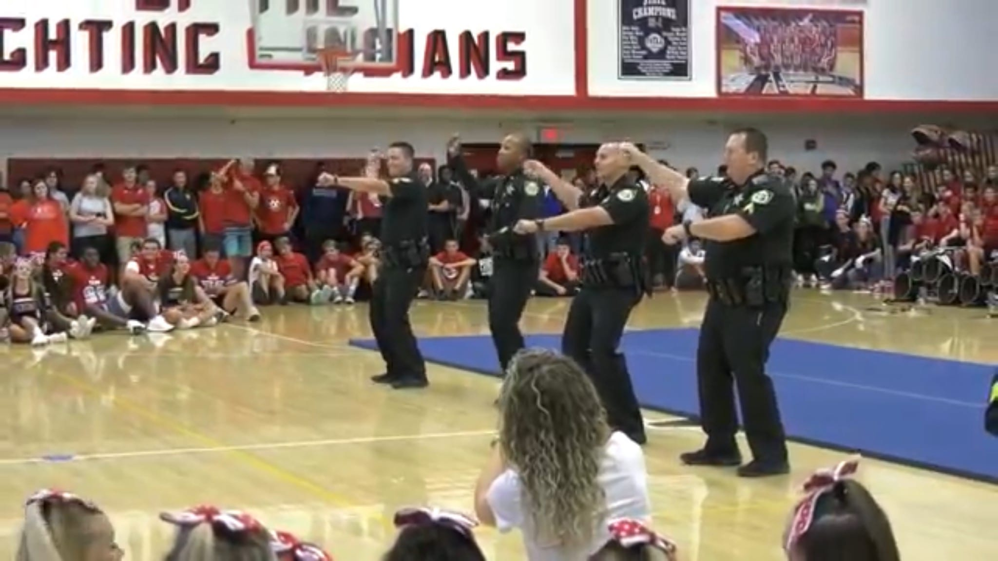 Police officers dance in front of students at high school pep rally. (Courtesy of Major Milo Thornton)