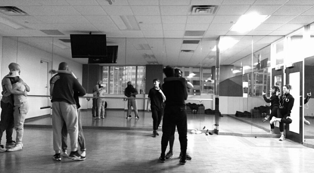 Dancers hugging inside dance studio