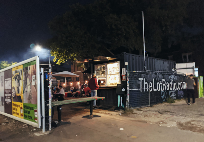 People at a bar made out of shipping containers.