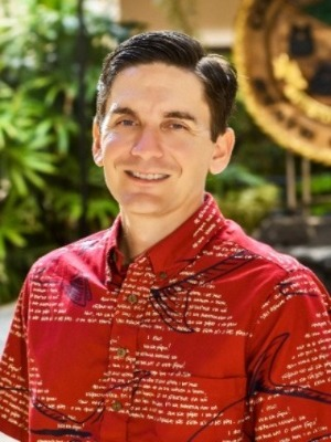 Justin Kollar is a white man with short, dark hair. He is smiling. He's wearing a red Aloha shirt with a white design.
