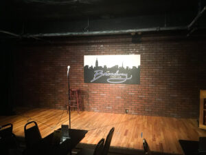 """Wooden stage with a mic and a sign that says """"The Broadway Comedy Club"""""""