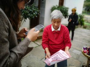 A woman with a cellphone scans a qr code held by an older woman