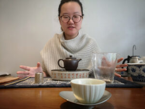 A woman seated behind a teapot and teacup, hands outstretched.