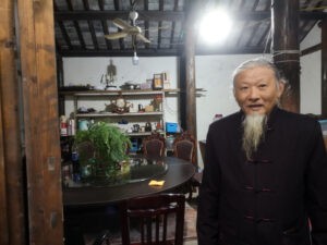 A man with a long chin beard stands before a roomy old dining room