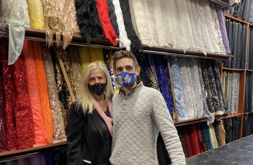 Tricia Fleishman and her son, Joshua, stand among colorful fabrics at their fabric store, Fleishman Fabrics, located on historic Fabric Row.