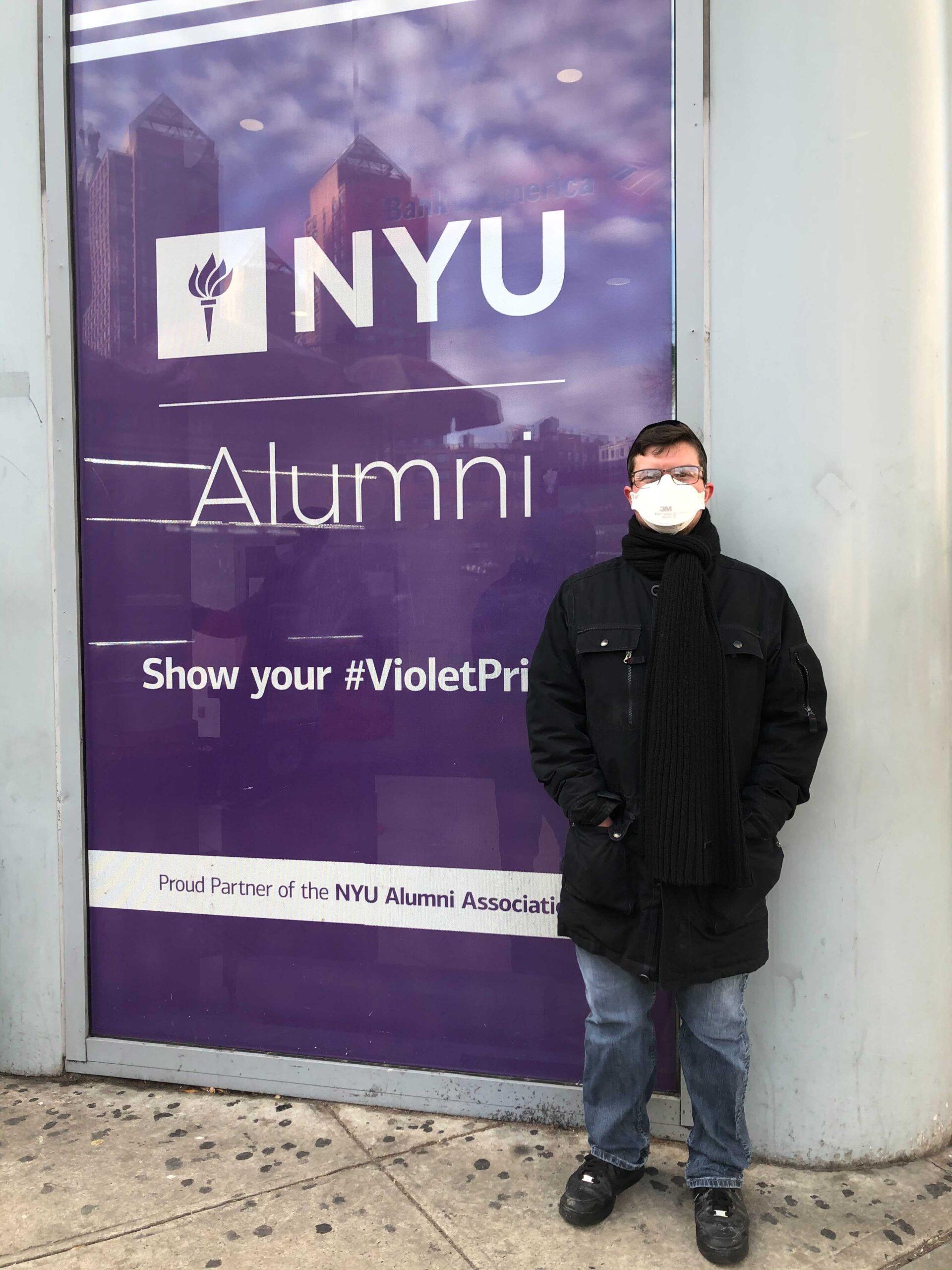 Caleb Bloomfield in front of NYU Alumni Display