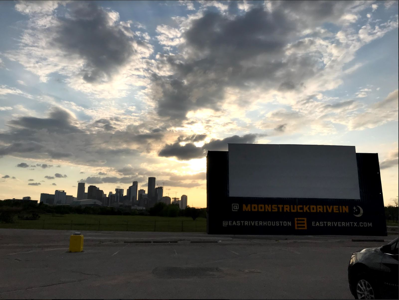 The sun begins to set over the Houston skyline before a movie begins rolling at Moonstruck Drive-In. [Credit: Corina Garcia]