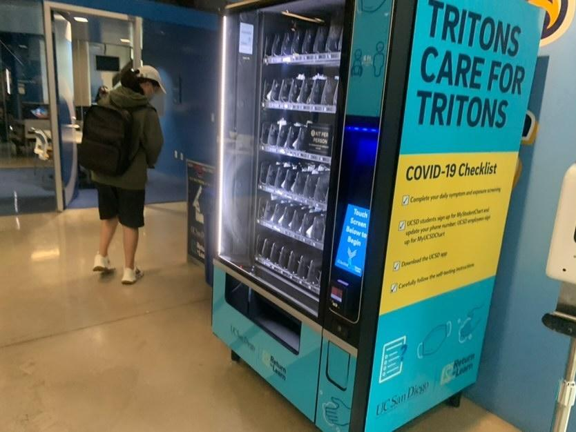UCSD Student buying her free COVID test from the Vending Machine.