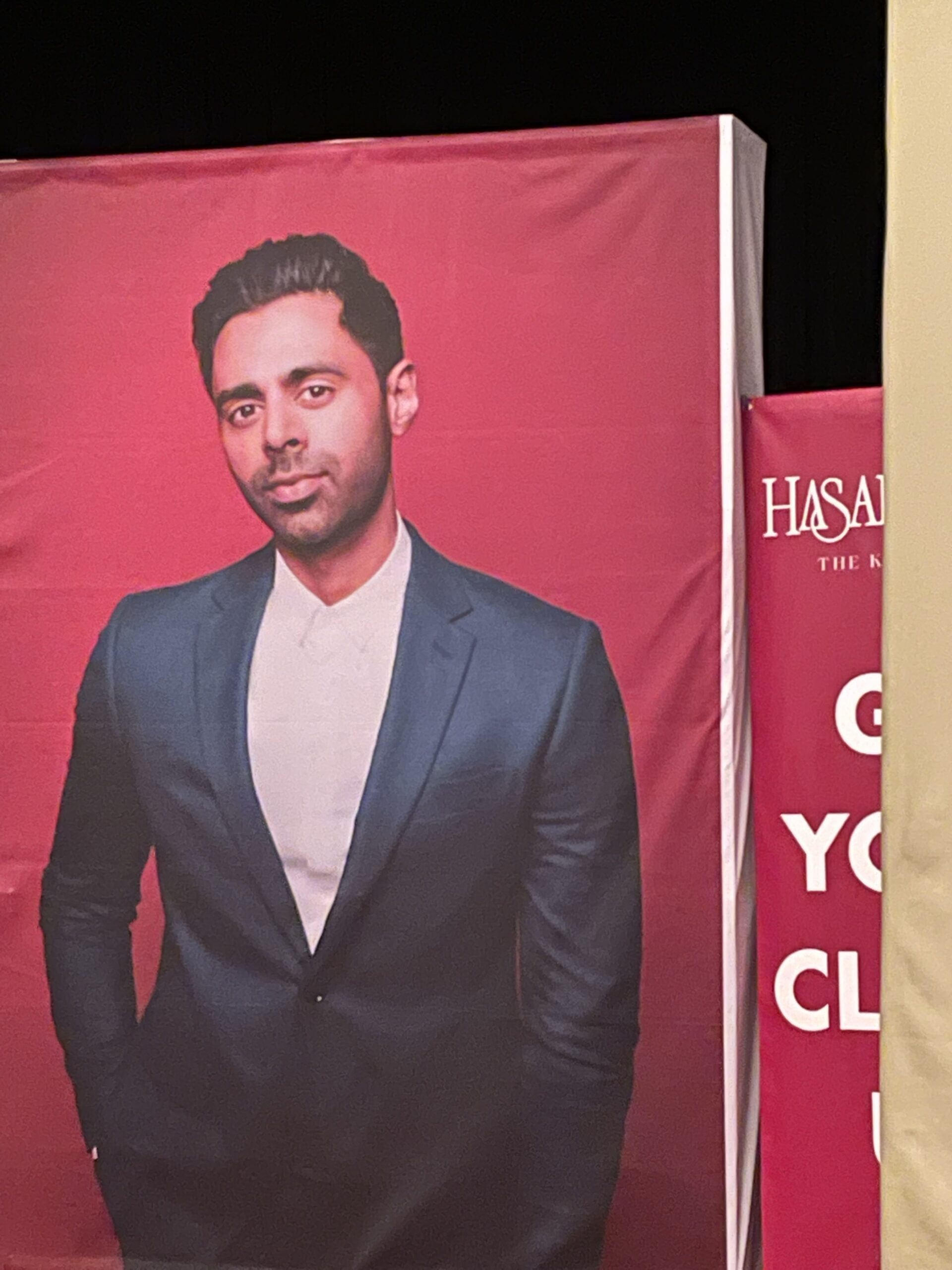 A poster of Hasan Minhaj shows the comedian wearing a dark suit against a bright red backdrop.