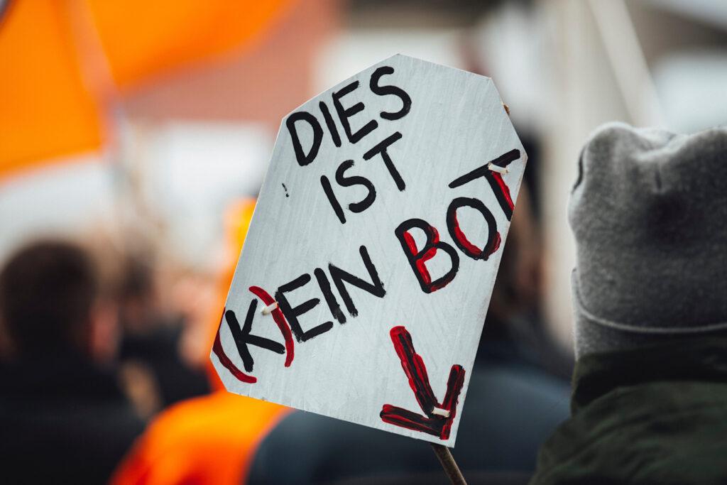 """A protest sign that reads """"Dies ist (K)ein Bot"""" with an arrow pointing down"""
