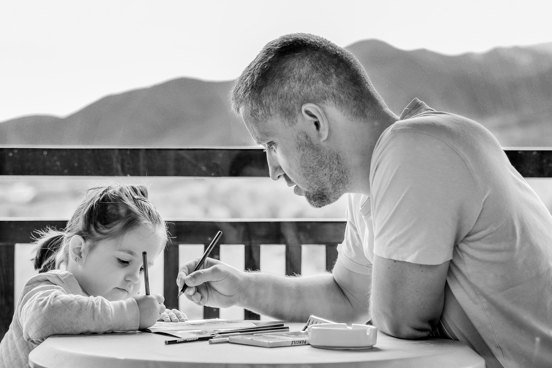 white dad and daughter coloring together